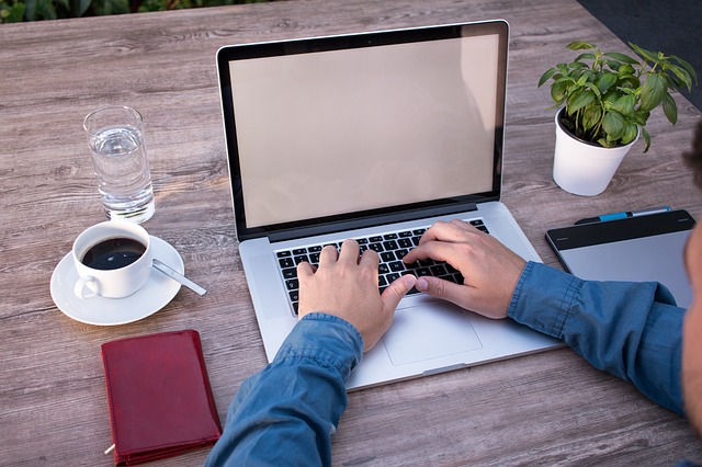 člověk u počítače, notebook na dřevěném stole, vedle káva, voda a zelená kytka
